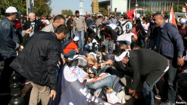 Wounded people on the ground as survivors offer help after an explosion during a peace march in Ankara, Turkey.