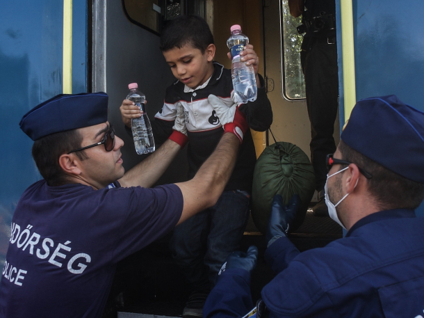 Hungarian police officers help a Syrian child at the railway station in Roszke, Hungary, on Monday. Thomas Campean / Anadolu Agency / Getty Images