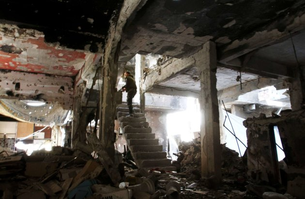 A man climbed a staircase inside a demolished building in the Yarmuk refugee camp near the Syrian capital of Damascus on Monday.