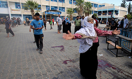 A Palestinian woman reacts as the blood of wounded and dead people is seen on the ground following what witnesses said was an Israeli air strike at a United Nations-run school, where displaced Palestinians take refuge, in Rafah in the southern Gaza Strip August 3, 2014 (Photo: Reuters)