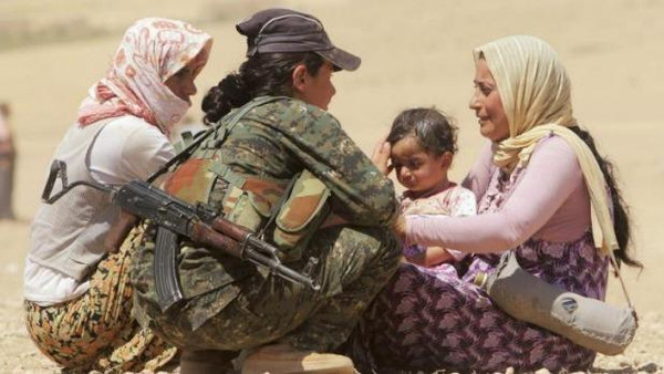 Displaced people from the minority Yazidi sect speak with a Kurdish fighter near the border between Iraq and Syria's Hasaka province. (File photo: Reuters)