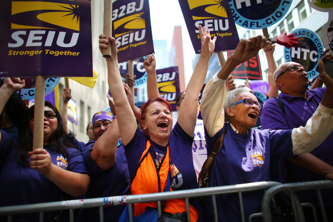 Fast-food workers and supporters gathered on Wednesday in Manhattan to watch a live video of the wage board's decision. The governor hailed it as an example of New York's progressiveness.  Credit Chang W. Lee/The New York Times