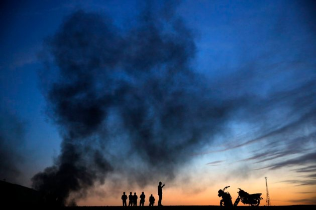 Kurdish refugees stand and walk on a hilltop as thick smoke rises from the Syrian town of Kobani during heavy fighting between Islamic State and Kurdish Peshmerga forces in Sanliurfa province, Turkey on Oct. 26, 2014.