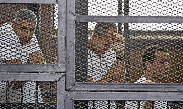 From left, Mohammed Fahmy, Canadian-Egyptian acting bureau chief of Al-Jazeera, Australian correspondent Peter Greste, and Egyptian producer Baher Mohamed in a Cairo court. Photograph: Hamada Elrasam/AP
