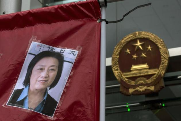 A portrait of Chinese journalist Gao Yu is displayed by a protester in front of the national emblem of China during a demonstration calling for the release of Gao outside the Chinese liaison office in Hong Kong May 11, 2014.