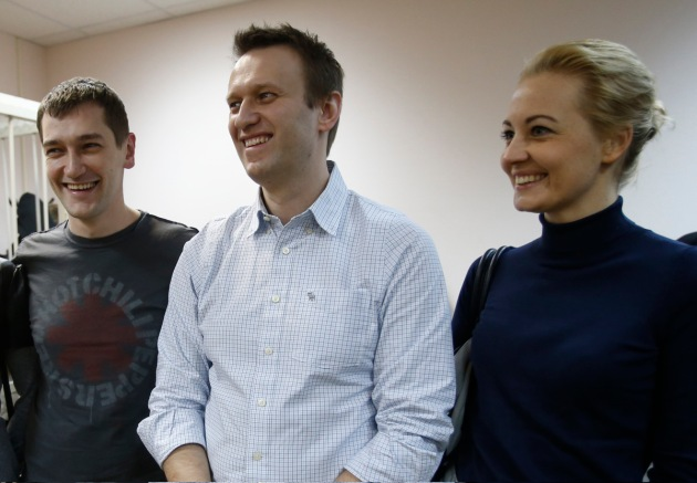 Russian opposition activist and anti-corruption crusader Alexei Navalny, 38, center, his wife Yulia and his brother Oleg Navalny smile at a court in Moscow on Dec. 30, 2014.