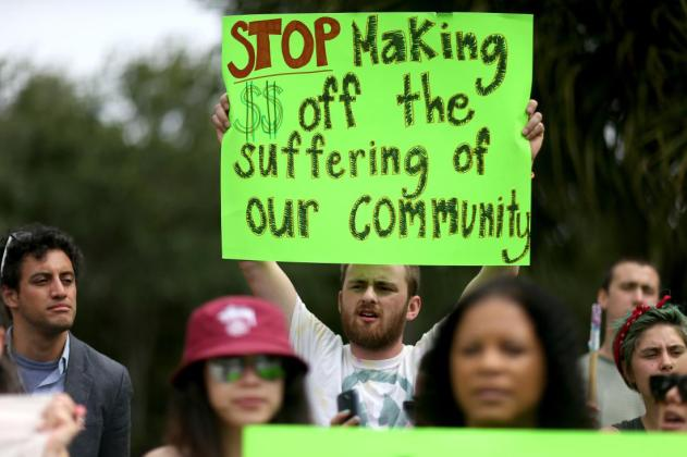 BOCA RATON, FL - MAY 04: Protesters gather in front of the GEO Group headquarters to speak out against the company that manages private prisons across the United States on May 4, 2015 in Boca Raton, Florida. The protesters are condemning what they say are the companies active lobbying efforts to criminalize and imprison immigrants and people of color and then to make a profit off their imprisonment. (Photo by Joe Raedle/Getty Images)