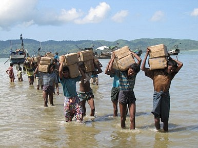 Displaced Rohingya unload provisions from a boat. Image Credit: Mathias Eick, EU/ECHO