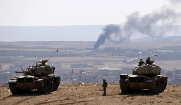 Smoke rises from the Syrian town of Kobane, Turkish army tanks take position on the Turkish side of the border, October 8, 2014. Umit Bektas/Reuters