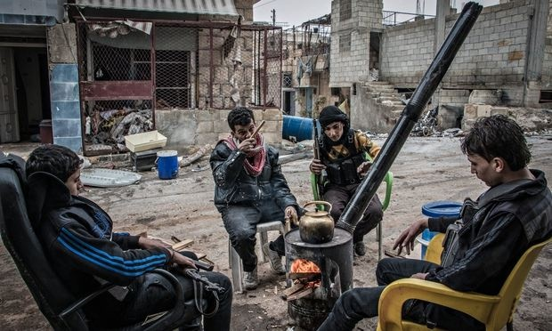 A group of rebel fighters sit around a fire in Aleppo. Photograph: Karam Almasri/NurPhoto/Rex Features