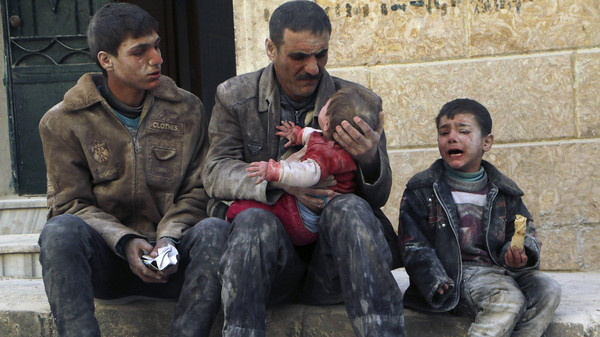 A man holds a baby saved from under rubble, who survived what activists say was an air strike by forces loyal to Syrian President Bashar al-Assad, in Masaken Hanano in Aleppo, in this Feb. 14, 2014. (File Photo: Reuters)