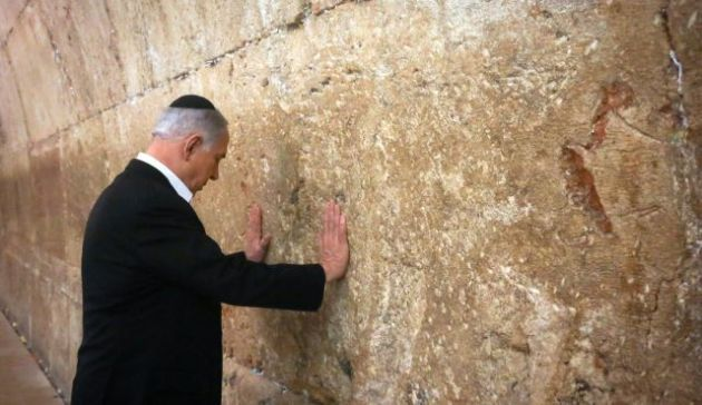 Israel's Prime Minister Benjamin Netanyahu touches the Western Wall during a visit in Jerusalem's Old City, Feb. 28, 2015.