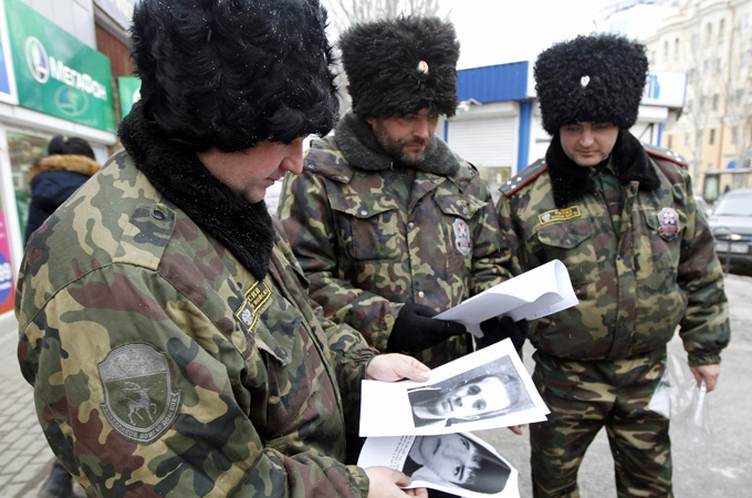 Russian security officers look at portraits of people suspected of involvement in terrorist acts [Reuters]