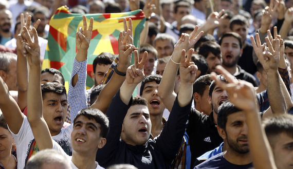 Kurdish demonstrators gesture as Selahattin Demirtas, co-chair of the HDP, Turkey's leading Kurdish party, addresses a crowd in Diyarbakir October 9, 2014. A three-week battle for the Syrian border town of Kobani has also led to the worst streets clashes in years between police and Kurdish protesters across the frontier in southeast Turkey. In Diyarbakir, Turkey's biggest Kurdish city, five people were killed in clashes on Monday and Tuesday between Islamist groups and PKK supporters, a senior police officer said.   REUTERS/Osman Orsal (TURKEY - Tags: POLITICS CIVIL UNREST) - RTR49ICE