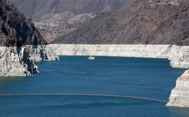 "A paddle wheeler and a small motorboat sail on Lake Mead, North America's largest man-made reservoir. The water is at its lowest level since the Hoover Dam was built in the 1930s. The white ""bathtub ring"" of mineral deposits on the rocks marks past water levels."