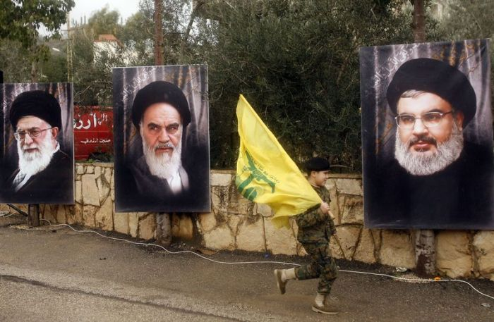A Lebanese boy carries a Lebanese flag past portraits of Iranian Supreme Leader Khamenei, former Supreme Leader and national founder Ruhollah Khomeini, and Hezbollah leader Hassan Nasrallah (MAHMOUD ZAYYAT/AFP/Getty)