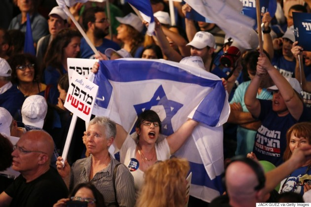 An Israeli protester waves a national flag during a rally in Rabin Square, Tel Aviv on March 7, 2015. (JACK GUEZ/AFP/Getty Images)