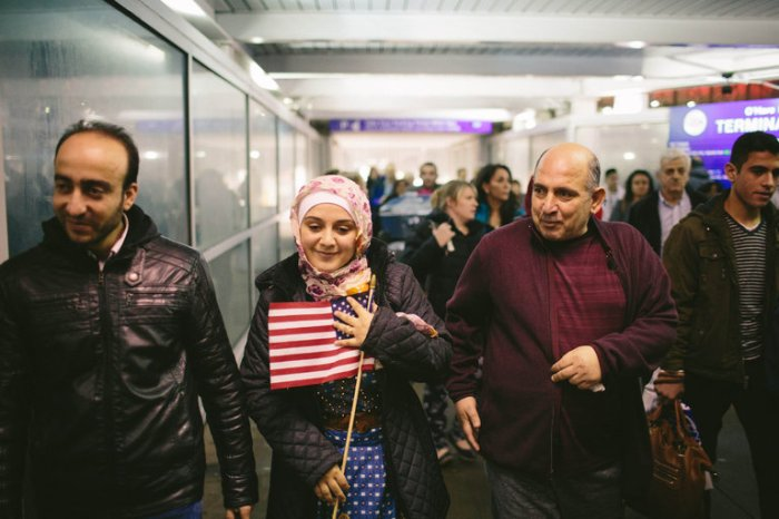 From left, Abdulmajeed and his wife, Baraa, Syrian refugees, were greeted by her father at O'Hare International Airport in Chicago on Tuesday. They were allowed to enter the country after a federal judge blocked key parts of President Trump's immigration ban.  Credit Alyssa Schukar for The New York Times