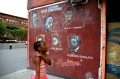 A girl walks by a mural featuring Malcolm X in New York City. (Photo: Tarnie)