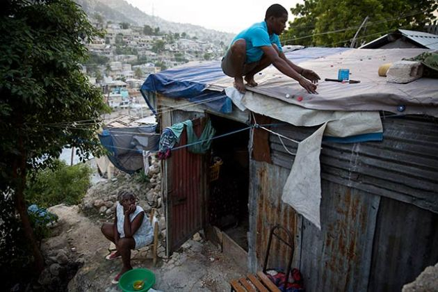 Nadain Javier repairs the leaking roof of his makeshift house in the earthquake-ravaged neighborhood of Campeche, in Port-au-Prince, Haiti, December 6, 2012. The Red Cross promised to build hundreds of new homes in Campeche but none have been built. (Photo: Damon Winter/The New York Times)