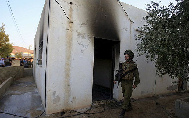 An Israeli soldier walks past a house that had been torched in a suspected attack by Jewish extremists killing an 18-month-old Palestinian child, injuring a four-year-old brother and both their parents at Kafr Duma village near the West Bank city of Nablus July 31, 2015. Photo: Reuters