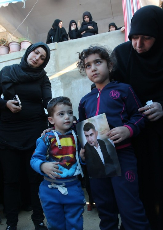 Ali and Malak, the children of Adel Termos, who was killed in a twin bombing attack that rocked a busy shopping street in the area of Burj al-Barajneh in Beirut's southern suburb, carry a portrait of their father during his funeral in the village of Tallussa in the Nabatiyeh governorate, south of Lebanon, on Nov. 13, 2015. (Mahmoud Sayyat/AFP/Getty Images)