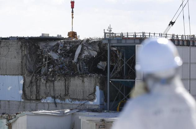 A member of the media, wearing a protective suit and a mask, looks at the No. 3 reactor building at Tokyo Electric Power Co's (TEPCO) tsunami-crippled Fukushima Daiichi nuclear power plant in Okuma town, Fukushima prefecture, Japan. Toru Hanai/Files/Reuters