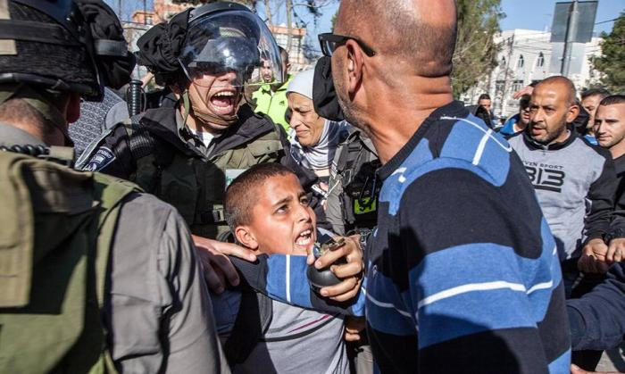 Israeli border police arresting Ahmad Abu Sbitan, 11, in front of his school in East Jerusalem. The police accused him of throwing a stone at them. © Majd Gaith