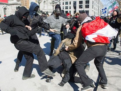 Anti-fascists, left, clash with opposing protesters during a demonstration regarding motion M-103 in Montreal, Saturday, March 4, 2017. THE CANADIAN PRESS/Graham Hughes ORG XMIT: GMH103