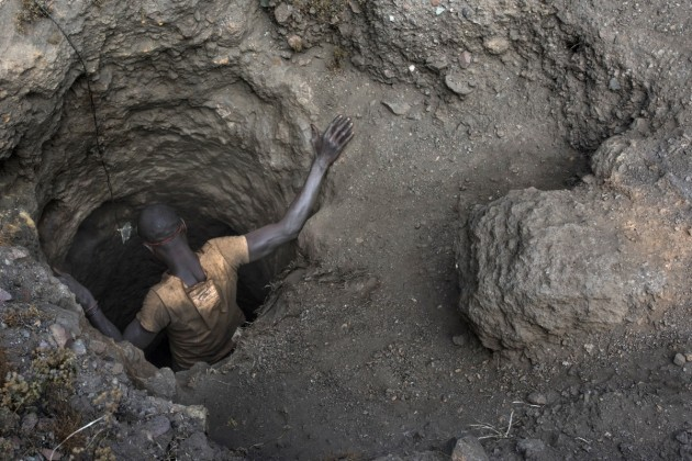 """A """"creuseur"""" descends into a tunnel at the mine in Kawama. The tunnels are dug with hand tools and burrow deep underground."""