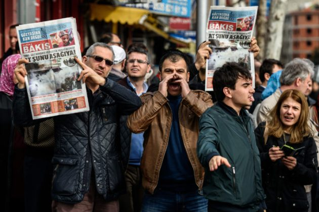 "Protesters hold up a new newspaper by the former team of Zaman called ""Yarina Bakis"" (""Look to tomorrow"") during a demonstration near the headquarters of the newspaper Zaman in Istanbul on March 6, 2016. Turkish police on March 4 raided the Istanbul premises of the Zaman newspaper using tear gas and water cannon to enter the building in order to impose a court order placing the media business under administration. The front page of the paper, normally strongly critical of the president, on March 6 was full of articles supporting the government. / AFP / OZAN KOSE (Photo credit should read OZAN KOSE/AFP/Getty Images)"