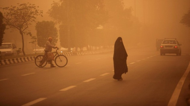 """Iranians cross a street as a heavy sand storm hits the city of Ahvaz in the southwestern province of Khuzestan on April 13, 2011 as """"unprecedented"""" sandstorms mostly originating from neighbouring Iraq hit 20 provinces, forcing the shutdown of schools and government offices. AFP PHOTO/MOHAMMAD REZA DEHDARI / AFP PHOTO / MOHAMMAD REZA DEHDARI"""